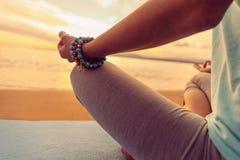 Woman meditating in pose of lotus, close-up. Woman meditating in pose of lotus on beach in summer, close-up Stock Photo