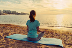 Woman meditating in pose of lotus at sunset Royalty Free Stock Images