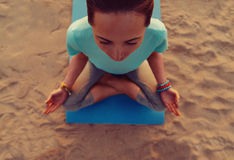 Woman meditating in pose of lotus. Young woman meditating in pose of lotus on beach, top view Stock Image