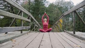 Woman meditating practicing yoga in the forest Padmasana asana. 4k slow motion stock video footage