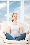 Woman meditating, relaxing, sitting in a lotus position on the Royalty Free Stock Images