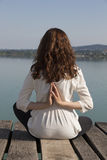 Woman meditating in reverse namaste pose during yoga by lake. Back of a young woman is sitting in reverse namaste pose by lake Royalty Free Stock Photo