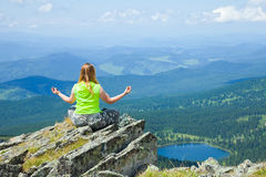 Woman meditating on rock Royalty Free Stock Images