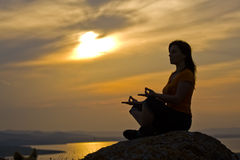 Woman meditating on a rock. Silhouette of a beautiful woman meditating on a rock at the sunset Royalty Free Stock Photos