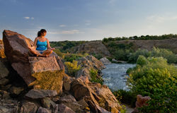 Woman meditating on a rock above a river Stock Photo