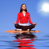 Woman meditating on rocks Stock Images