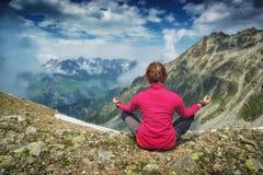 Woman meditating on the rocky hill. Woman meditating in sitting yoga position on the rocky hill above Caucasus mountain valley. Svaneti region, Georgia Royalty Free Stock Photo