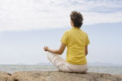 Woman meditating at the sea royalty free stock image