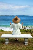 A Woman Meditating by the Sea Stock Image