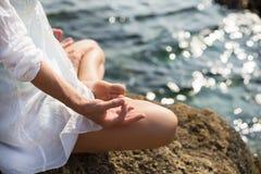 Woman meditating at the sea. Serenity and yoga practicing at sunset, meditation Royalty Free Stock Image