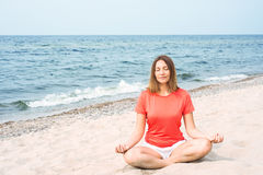 Woman meditating by the sea Stock Photo