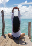 Woman meditating by the sea Stock Photos