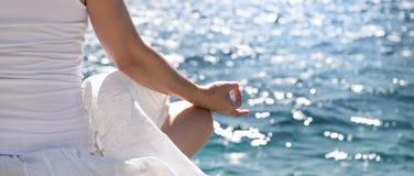 Woman meditating at the sea Stock Photo