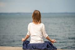 Woman meditating at the sea Stock Images