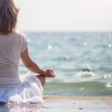 Woman meditating at the sea Stock Image