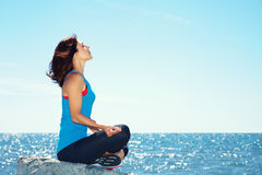 Woman meditating on the sea shore. Young beautiful woman meditating on the sea shore on a background of water Stock Photography