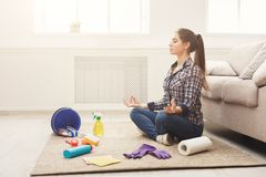 Woman meditating while cleaning home. Woman meditating, sitting on carpet while cleaning home in the living-room, copy space. Housekeeping and home cleaning Stock Photo