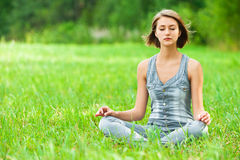 Woman meditating sitting on grass. Young, attractive woman sitting on green grass (meadow, glade) cross-legged in lotus position meditating Stock Photos