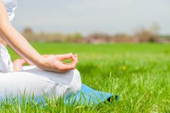 Woman is meditating sitting in Lotus pose on grass at the park stock images