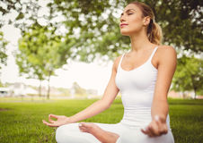 Woman meditating while sitting in lotus pose Stock Image