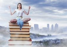 Woman meditating sitting meditating on Books stacked by distant city Stock Images