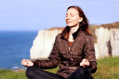 Woman meditating smiling in yoga pose on top of Normandy cliffs in the spring. Beautiful serene Caucasian female model relaxing in yoga pose and smiling out on stock image