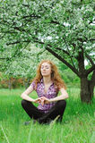 Woman meditating under blooming tree Stock Photos