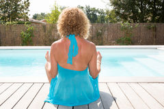 Woman meditating on a wooden deck under tranquil blue water Royalty Free Stock Images