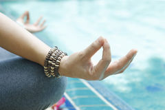 Woman meditating with wrist beads in a lotus yoga position at blue swimming pool Royalty Free Stock Photo
