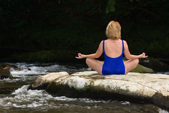 Woman meditating with yoga. Woman meditating with yoga on a flat river rock Royalty Free Stock Images