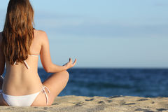 Woman meditating yoga on the beach in summer. With the horizon over the sea in the background Stock Photo