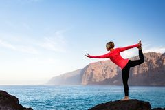 Woman meditating in yoga dancer pose, inspiring landscape. Woman meditating in yoga dancer poseNatarajasana over ocean and islands, coastline and rocky mountains Royalty Free Stock Photos