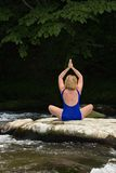 Woman meditating with yoga on a flat river rock. Royalty Free Stock Photos