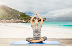Woman meditating in yoga lotus pose on beach. Fitness, sport and people concept - woman meditating in yoga lotus pose on mat over exotic tropical beach Royalty Free Stock Images