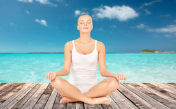 Woman meditating in yoga lotus pose Stock Photography