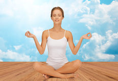 Woman meditating in yoga lotus pose Stock Image