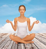 Woman  meditating in yoga lotus pose Royalty Free Stock Image