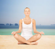 Woman  meditating in yoga lotus pose Royalty Free Stock Photo