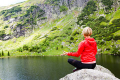 Woman meditating in yoga pose in front of mountain lake Stock Image