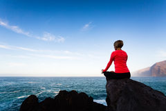 Woman meditating in yoga pose, ocean view Stock Image