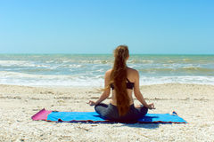 Woman meditating in yoga pose outdoors. A woman with long hair is facing away from viewer looking at the sea while mediataing outside at the beach in yoga lotus Stock Photos