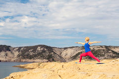 Woman meditating in yoga pose at the sea and mountains Royalty Free Stock Photo