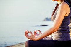 The woman meditating in a yoga pose on the tropical beach. Femal Stock Photos