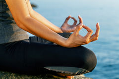 The woman meditating in a yoga pose on the tropical beach. Femal Stock Photography
