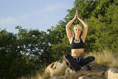 Woman meditating yoga on rock Royalty Free Stock Photo
