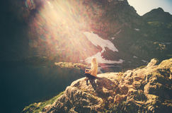 Woman meditating yoga sitting on cliff alone sun light Royalty Free Stock Photo