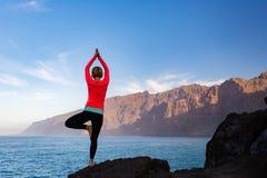 Woman meditating in yoga vrksasana tree pose royalty free stock images