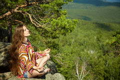 Woman meditating. Young beautiful woman meditating at the mountains. relaxation outdoors. nature freedom and inspiration Stock Image