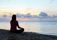 Woman meditation on the beach stock images