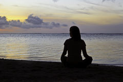 Woman meditation on the beach Stock Image